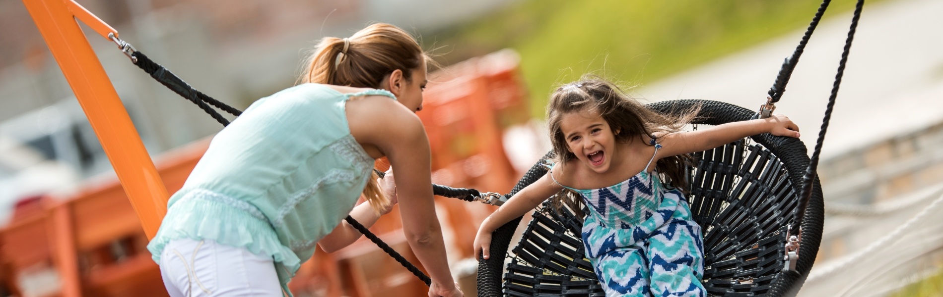 Image of a woman pushing a young girl on a basket swing in a playground
