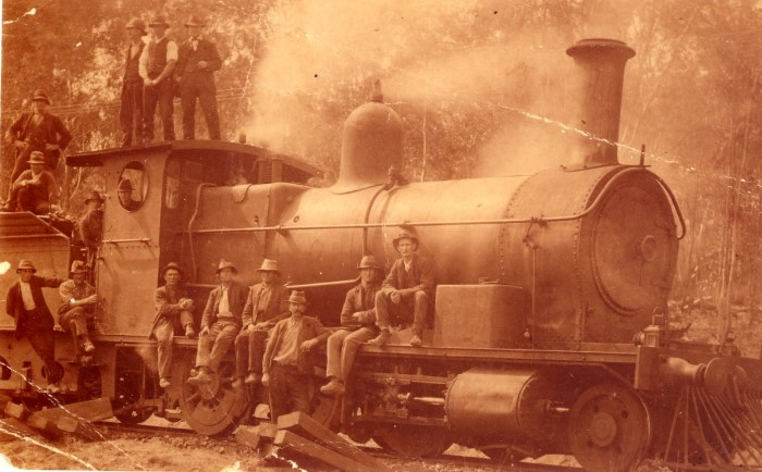 An old sepia photograph of a steam train and the work men around it
