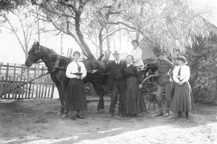 A family portrait in fromt of a horse and cart