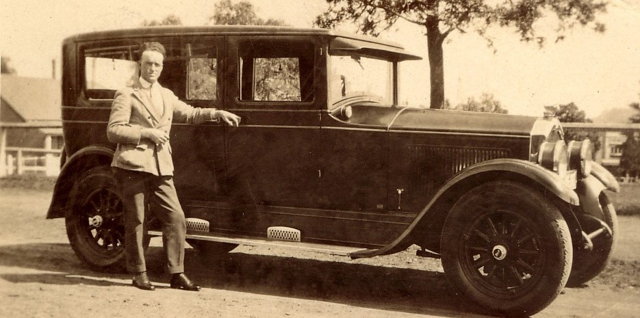 A well dressed gentleman leaning on his car