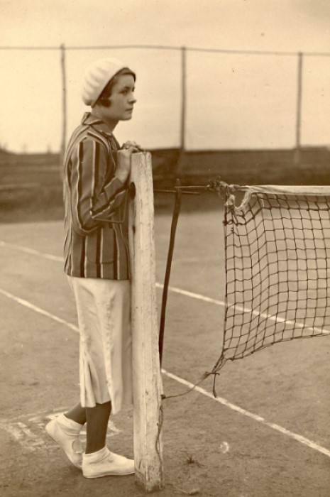 A young woman in tennis clothes from the 1930s era waiting next to the court