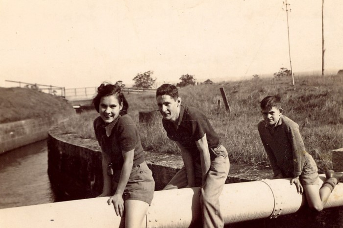3 teenagers sitting on a large water pipe over a canal