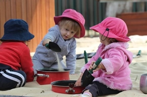 Three young children playing with pots and pans in the sand pit