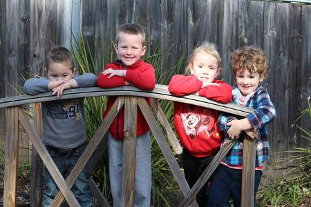 Four boys standing on wooden garden bridge at service