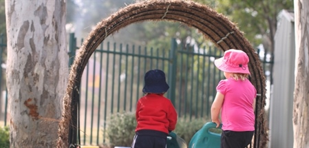Children walking through thatch archway