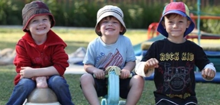 Three boys with cheeky smiles, two on trikes and the third kneeling down and pretending he is on a trike