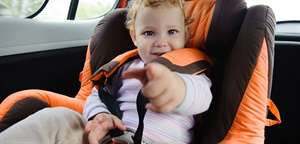 Child in orange and black car seat