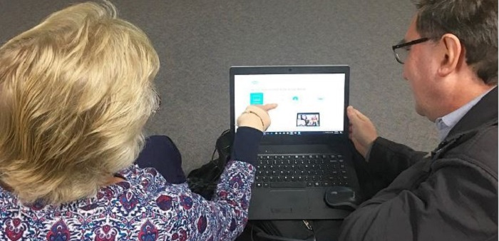 Staff teaching woman about technology on a laptop
