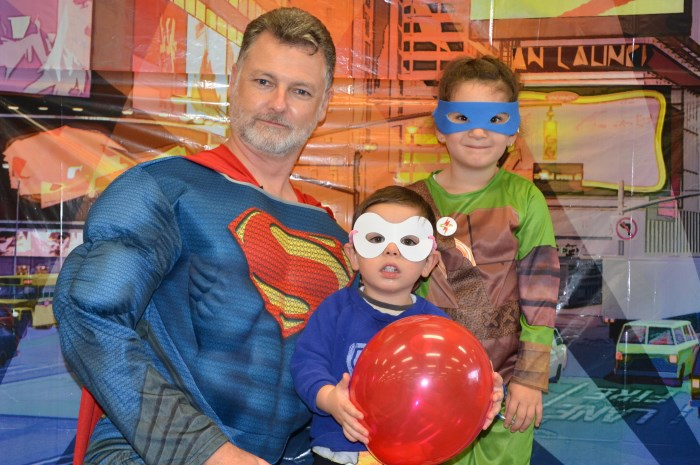 Superman character with 2 young children dressed in super hero costumes