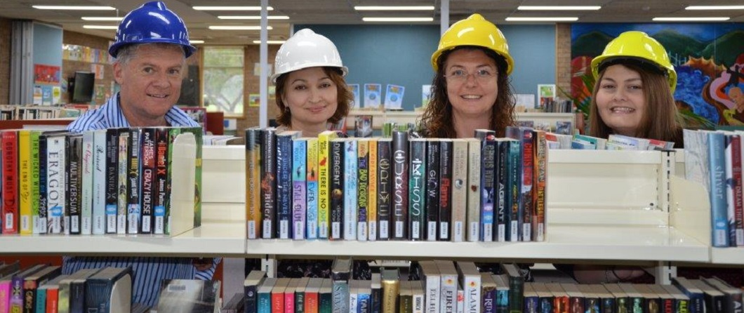 Image of book shelves with 4 staff in construction helmets