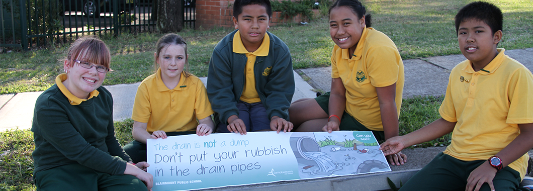 students from Blairmount Primary School, displaying their educational artwork that aencourages people not to litter in their community