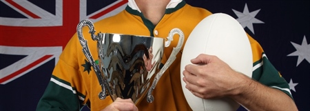 A man dressed in a yellow and gold jersey holding a trophy in one hand and a ball in the other. An Australian flag is in the background.