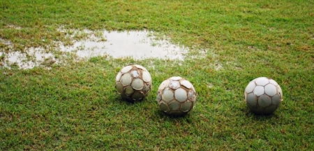 3 footballs on a football field with puddles of water